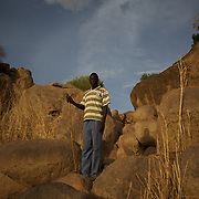 April 28, 2012 - Buram, Nuba Mountains, South Kordofan, Sudan: A Nuba man stands among rocks in the mountains outside Buram village in South Kordofan's Nuba Mountains...Since the 6th of June 2011, the Sudan's Army Forces (SAF) initiated, under direct orders from President Bashir, an attack campaign against civil areas throughout the South Kordofan's province. Hundreds have been killed and many more injured...Local residents, of Nuba origin, have since lived in fear and the majority moved from their homes to caves in the nearby mountains. Others chose to find refuge in South Sudan, driven by the lack of food cause by the agriculture production halt due to the constant bombardments of rural areas. (Paulo Nunes dos Santos/Polaris)