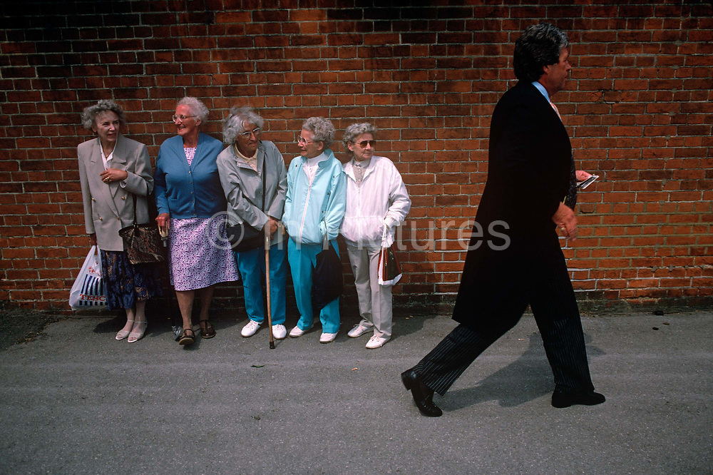 Five elderly women on-lookers are lined against a wall outside the famous Ascot race course on Ladies' Day, the annual event on the English sporting and social calendar in June. Each are standing in order of size, from tallest (who holds a Tesco supermarket bag) to smallest and watch as a posh racegoer arrives for the day's racing dressed in a formal jacket and tails and will also have on red Ascot badges allowing him entry to this exclusive royal event attended by the Royal Family and the hoi polloi of English society. We see the two sides of the class system but it is a humorous scene. There is good nature between the two groups with smiles exchanged but here the man strides past knowing he is under inspection from the common people.