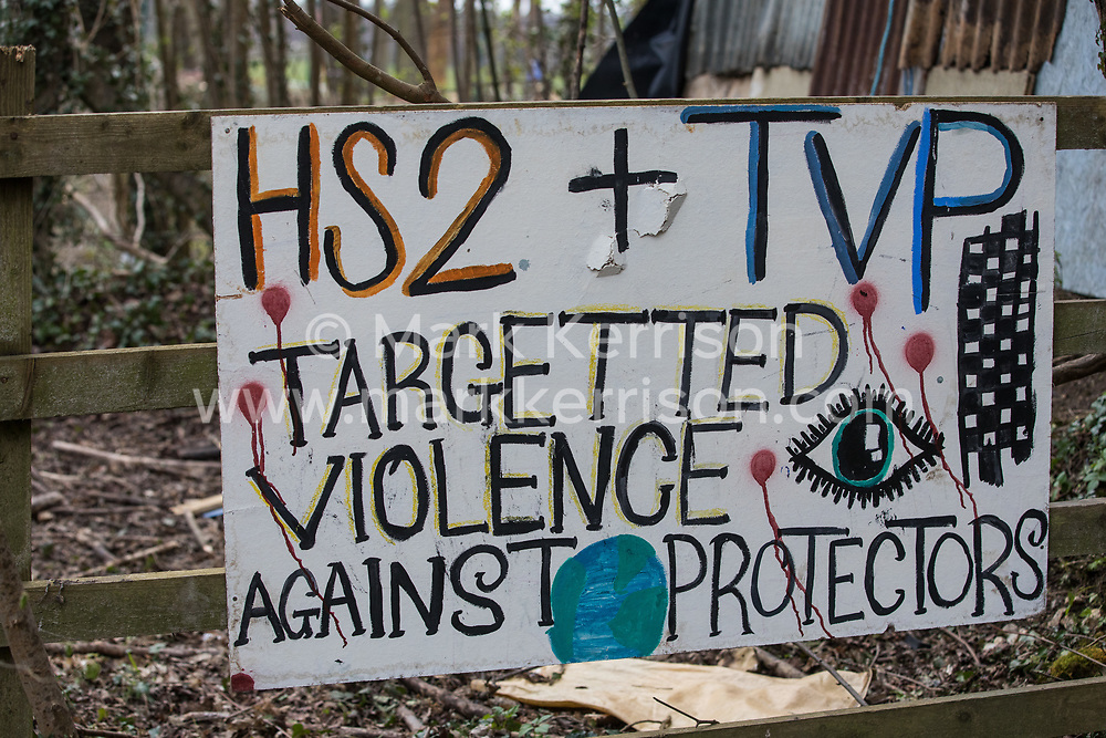Wendover, UK. 9th April, 2021. A sign suggesting that HS2 and Thames Valley Police use 'targeted violence' against tree protectors is pictured outside Wendover Active Resistance Camp, which is occupied by activists opposed to the HS2 high-speed rail link. Tree felling work for the project is now taking place at several locations between Great Missenden and Wendover in the Chilterns AONB, including opposite the camp.