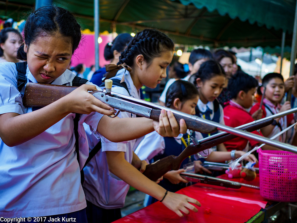 """03 NOVEMBER 2017 - BANGKOK, THAILAND:  Girls shoot air rifles in an arcade during Loi Krathong at Wat Prayurawongsawat on the Thonburi side of the Chao Phraya River. Loi Krathong is translated as """"to float (Loi) a basket (Krathong)"""", and comes from the tradition of making krathong or buoyant, decorated baskets, which are then floated on a river to make merit. On the night of the full moon of the 12th lunar month (usually November), Thais launch their krathong on a river, canal or a pond, making a wish as they do so. Loi Krathong is also celebrated in other Theravada Buddhist countries like Myanmar, where it is called the Tazaungdaing Festival, and Cambodia, where it is called Bon Om Tuk.    PHOTO BY JACK KURTZ"""