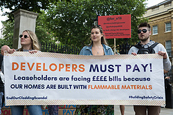 Campaigners hold a banner reading Developers Must Pay at a protest opposite Downing Street by leaseholders and tenants living in unsafe homes on 15th July 2021 in London, United Kingdom. Some leaseholders are faced with crippling costs to fix safety issues and they called on the government to ensure that their homes are made safe from fire as a matter of priority, to make interim payments and to cover fire safety remediation costs and to find a solution with mortgage lenders which enables them to move on with their lives.