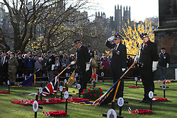 Standard bearers lower their Colour Flags as people observe a two minute silence in memory of those who have fallen in conflict during a service of Remembrance at the Edinburgh Garden of Remembrance in East Princes Street Gardens, Edinburgh.