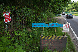 Wendover, UK. 16th June, 2021. Signs alongside the A413 outside Stop HS2's Wendover Active Resistance Camp. Large areas of land around Wendover in the Chilterns AONB have already been cleared of trees and vegetation for the HS2 rail infrastructure project in spite of concerted opposition from local residents and environmental activists.