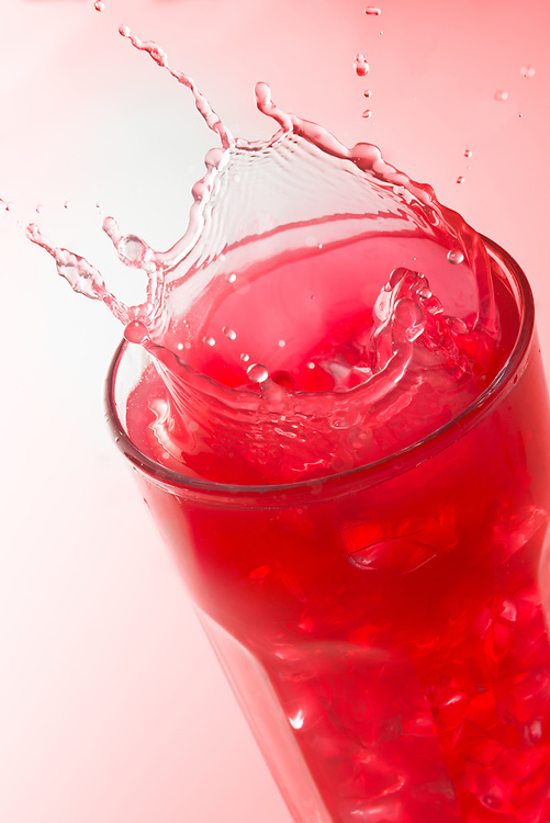 Close up of a splash on a glass of strawberry juice against a red background