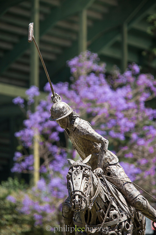 Statue of Polo player in front of Jacaranda tree, The Campo Argentina Del Polo, Buenos Aires, Argentina, South America