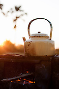 A kettle is boiled on a wood fire at a bush dinner of Abu Camp, a luxury safari camp in the Okavango Delta, Botswana