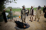 US Army Lieutenant Christopher Babcock looks at the body of a suspected Taliban fighter killed by US soldiers from 1-320th Alpha Battery, 2nd Brigade of the 101st Airborne Division, while local people protest the man was a farmer from Samir Kalacha village in the volatile Arghandab Valley, Kandahar, Afghanistan, Wednesday, July 28, 2010. (AP Photo/Rodrigo Abd)