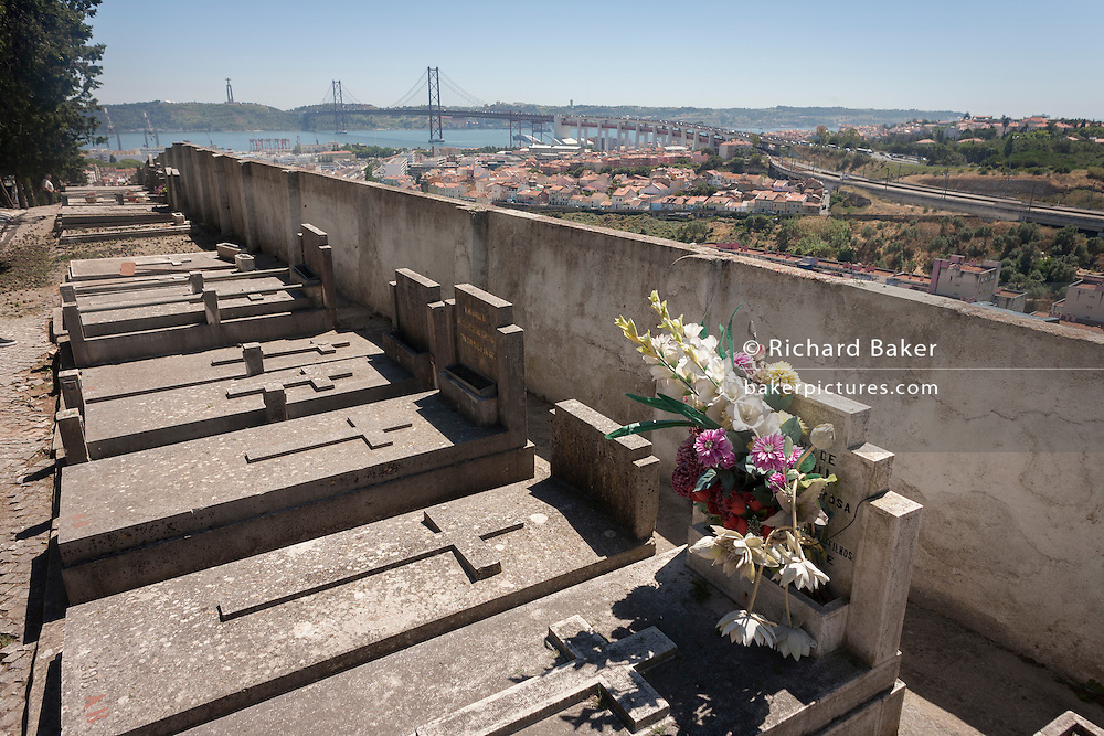 Graves and fading flowers overlook the Ponte 25 de Abril<br /> bridge and the district of Alacantara in the western Portuguese capital, on 14th July 2016, at Prazeres Cemetery, Lisbon, Portugal. Prazeres Cemetery (Cemitério dos Prazeres) is the largest cemetery in Lisbon, Portugal, located in the west part of the city in the former Prazeres parish. It was created in 1833 after the outbreak of a cholera epidemic. Many famous Portuguese citizens are buried here, including artists, authors and government figures, and the cemetery features many large mausoleums built in the 19th century. (Photo by Richard Baker / In Pictures via Getty Images)