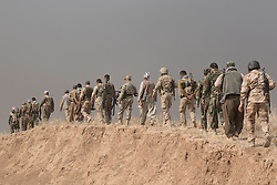 20/10/2016. Bashiqa, Iraq. Kurdish peshmerga forces move along an ISIS dug trench as take part in an offensive to retake the area around the Islamic State held city of Bashiqa, Iraq, today (20/10/2016).<br /> <br /> Launched in the early hours of today with support from coalition special forces and air strikes, the attack is part of the larger operation to retake Mosul from the Islamic State, and involves both the Kurds and the Iraqi Army. The city of Bashiqa, around 9 miles north of Mosul, is one of several gateway areas that must be taken before any attempted offensive on Mosul itself.<br /> <br /> Despite the peshmerga suffering several casualties after militants fought back using mortars, heavy machine guns and snipers, the Kurdish forces were quickly taking ground with Haider al-Abadi, the Iraqi prime minister, stating that the operation to retake Mosul was progressing faster than expected. Photo credit: Matt Cetti-Roberts/LNP