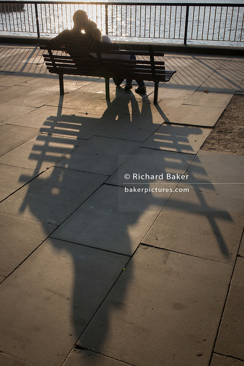 Couple share intimate moment in late afternoon on London's Southbank.