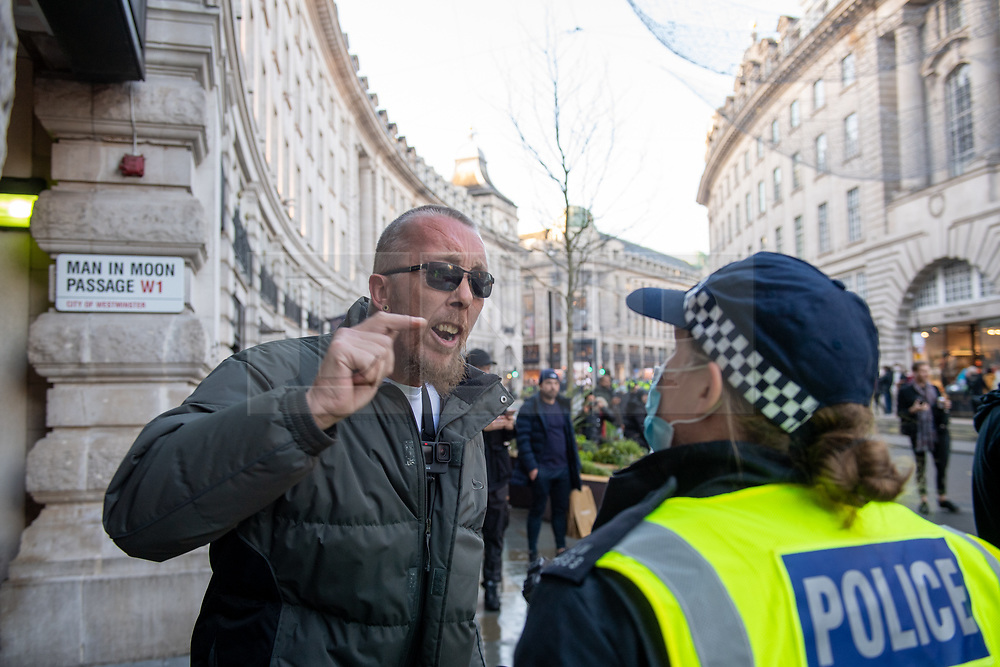 © Licensed to London News Pictures. 19/12/2020. London, UK. A man argues with a police officer on Regent Street. Protesters have gathered in central London for an anti-lockdown demonstration. Photo credit: Peter Manning/LNP
