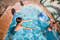 Father and son playing with ball in swimming pool, Mauritius