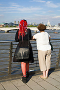 A couple, one an alternatively dressed woman looking across the River Thames at the skyline on Hungerford Bridge, London, UK