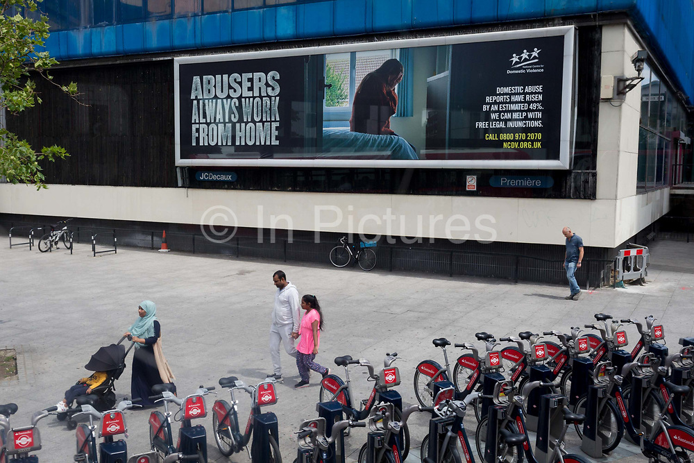 A family walk past a large billboard ad informing the public about domestic abuse during the Coronavirus pandemic lockdown which has seen a dramatic rise in domestic abuse cases in the UK, at Elephant & Castle, on 3rd July 2020, in London, England. The UK's largest domestic abuse charity, Refuge, has reported a 700% increase in calls to its helpline in a single day.