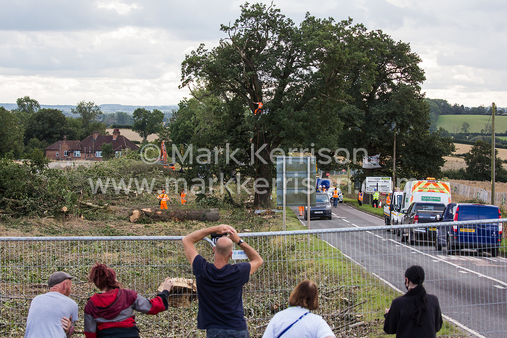 Offchurch, UK. 24th August, 2020. Anti-HS2 activists observe HS2 workers preparing to fell a mature oak tree after a fellow activist had occupied the tree alongside the Fosse Way in order to try to protect it from works in connection with the HS2 high-speed rail link. The controversial HS2 infrastructure project is currently expected to cost £106bn and will destroy or significantly impact many irreplaceable natural habitats, including 108 ancient woodlands.