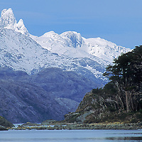 A rare sunny day illuminates Peninsula Roca above Fjord of the Mountains.  Tangled beech forests of the Cordillera Sarmiento are on the right.  The pinnacles are named Grupo La Paz.