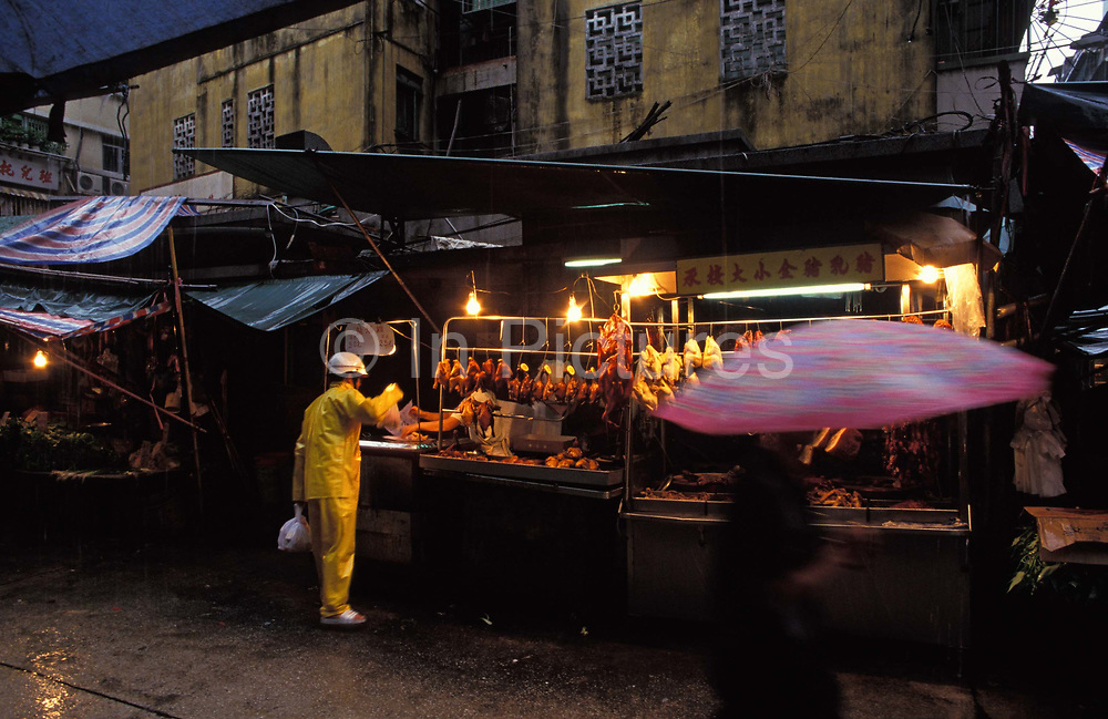 A passing shopper blurs while passing a market stall selling duck and chicken on a dark and typical rainy day in south-east Asia, on 10th August 1994, in Macau, China. Macau is now administered by China as a Special Economic Region SER, home to a population of mainland 95% Chinese, primarily Cantonese, Fujianese as well as some Hakka, Shanghainese and overseas Chinese immigrants from Southeast Asia and elsewhere. The remainder are of Portuguese or mixed Chinese-Portuguese ancestry, the so-called Macanese, as well as several thousand Filipino and Thai nationals. The official languages are Portuguese and Chinese.