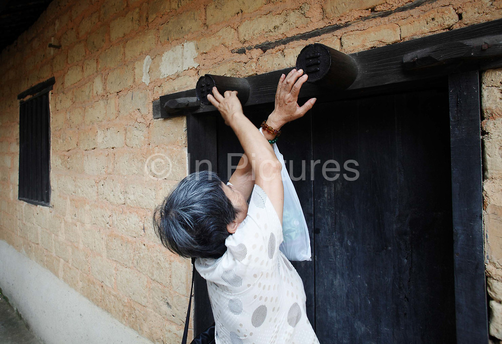 An elderly woman touches a door ornament for supposed good fortune at Mao Zedong's former home and birthplace in Shaoshan, Hunan Province, China on 12 August 2009.  The village of Shaoshan, in rural Hunan Province, is tiny in size but big in name. It was the childhood home for Mao Zedong, the controversial revolutionary who came from obscurity but eventually defied all odds conquered China in the name of communism. Now his home, a sacred place among China's official propaganda, is in reality a microcosm of the country itself: part commercialism, part superstition, with a dash of communist ideological flavor.