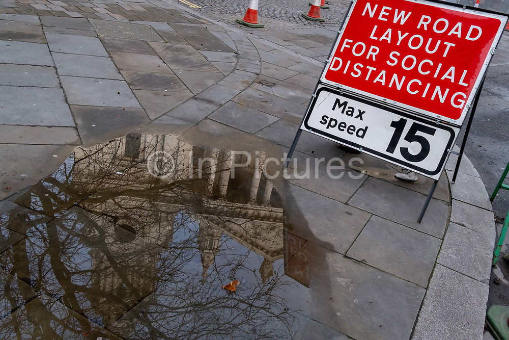 The reflection of St Pauls Cathedral is seen in a puddle on the pavement, alongside a traffic sign that warns drivers of a narrowing of the road, widened for social distancing pedestrians during the third lockdown of the Coronavirus pandemic, in the City of London, the capitals financial district, aka The Square Mile, on 2nd February 2021, in London, England.