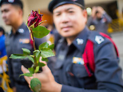 """14 FEBRUARY 2015 - BANGKOK, THAILAND: A Thai police officer holds a red rose handed out by a democracy protestor in Bangkok. Dozens of people gathered in front of the Bangkok Art and Culture Centre in Bangkok Saturday to hand out red roses and copies of George Orwell's """"1984."""" Protestors said they didn't support either Red Shirts or Yellow Shirts but wanted a return of democracy in Thailand. The protest was the largest protest since June 2014, against the military government of General Prayuth Chan-Ocha, who staged the coup against the elected government. Police made several arrests Saturday afternoon but the protest was not violent.      PHOTO BY JACK KURTZ"""
