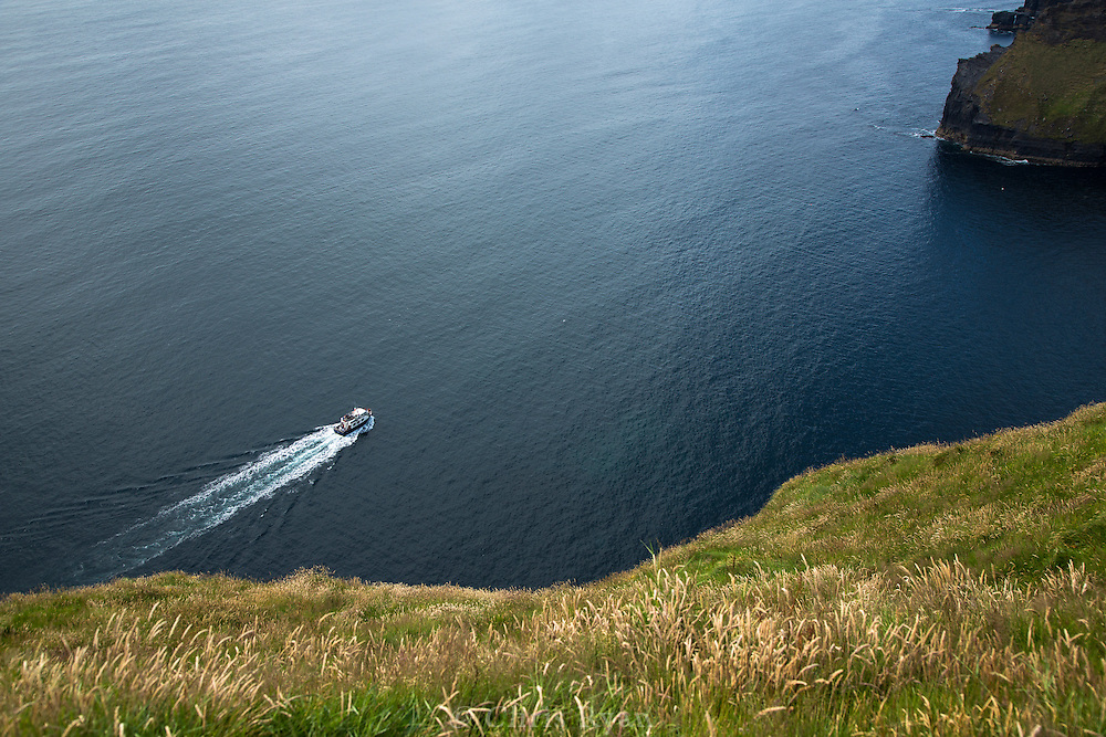 Tour boat plying the waters beneath the Cliffs of Moher