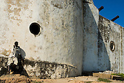 A boy leans against the fortified wall of Cape Coast castle in Cape Coast, Ghana on Saturday September 6, 2008. The fort was used during the slave trade as one of several exit points for slaves leaving Africa for the New World.