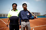 A player in the summer training camp run by Major League Baseball poses with his father, a fruit seller, in Wuxi, China, on 19 August, 2010.  Targeting teenagers between the ade of 12-15, the league hopes to use the camp to groom potential baseball talent in China and in the long term increase the popularity of the sport in the world's most populous country.