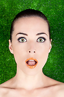 Closeup portrait of a surprised beautiful woman mouth open on green