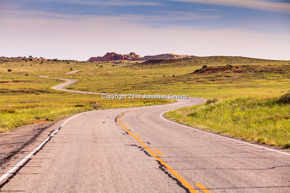A paved road winds through high desert meadows of Canyonlands National Park, Utah. WATERMARKS WILL NOT APPEAR ON PRINTS OR LICENSED IMAGES.<br /> <br /> Licensing: https://tandemstock.com/assets/72605421