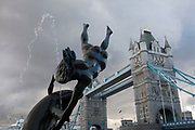 Famous fountain at Tower Bridge sends water into the sky. London, UK. The sculpture of a naked woman playing with a dolphin is called Girl with a Dolphin (1973) - by David Wynne.