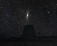 Every March at approximately 10PM, Andromeda has a close encounter with the iconic Devils Tower. When you look up at the stars, everything you can see with your eyes is contained within the Milky Way galaxy. But Andromeda is the exception. At 2.5 million light years away, it represents the farthest object visible to the naked eye. When you count the faint spiral arms, it is the same angular size in our sky as 6 full moons. Andromeda is thought to have about the same mass as our own galaxy. And just like the Milky Way, it is orbited by 2 satellite galaxies. Andromeda is actually best viewed in the fall, because that is when it's  highest in the sky. To get this picture I used a star tracking mount to capture greater detail, combined with an untracked image of the tower.
