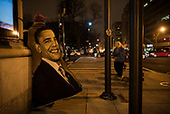 """Washington DC, USA - January 21, 2017: On the day of the Women's March, as night falls firmly on the city, a man wearing a """"pussy hat"""" and wrapped in a Barack Obama blanket leans against a building, watching a nearby protest."""