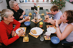 Family with teenage son with Downs Syndrome and daughter sitting around kitchen table eating breakfast,