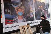 A woman wearting a face covering walks past a banner promoting the new book about bus travel during the Coronavirus pandemic by Glaswegian street photographer, Dougie Wallace aka Glasweegee, in Shoreditch, on 24th February 2021, in London, England.