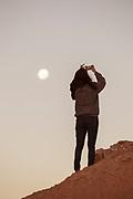 Tourist photographing the moon over desert, Valle de la Luna, Atacama Desert, Chile