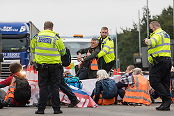A Metropolitan Police officer hauls an Insulate Britain climate activist out of a slip road from the M25 at Junction 25 after it was blocked twice in a single morning as part of a campaign intended to push the UK government to make significant legislative change to start lowering emissions on 15th September 2021 in Enfield, United Kingdom. The activists, who wrote to Prime Minister Boris Johnson on 13th August, are demanding that the government immediately promises both to fully fund and ensure the insulation of all social housing in Britain by 2025 and to produce within four months a legally binding national plan to fully fund and ensure the full low-energy and low-carbon whole-house retrofit, with no externalised costs, of all homes in Britain by 2030 as part of a just transition to full decarbonisation of all parts of society and the economy.