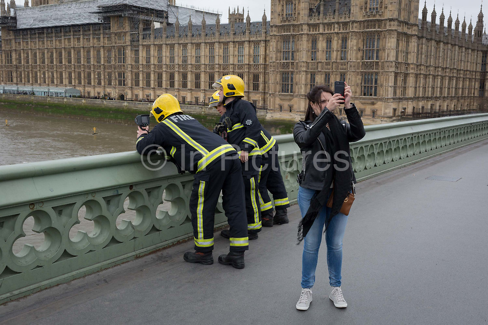 While a tourist takes a selfie, firefighters with the London Fire Brigade use a heat-seeking camera, looking down into the River Thames waters to search for a person who jumped off Westminster Bridge, on 29th March 2017, in London, England.