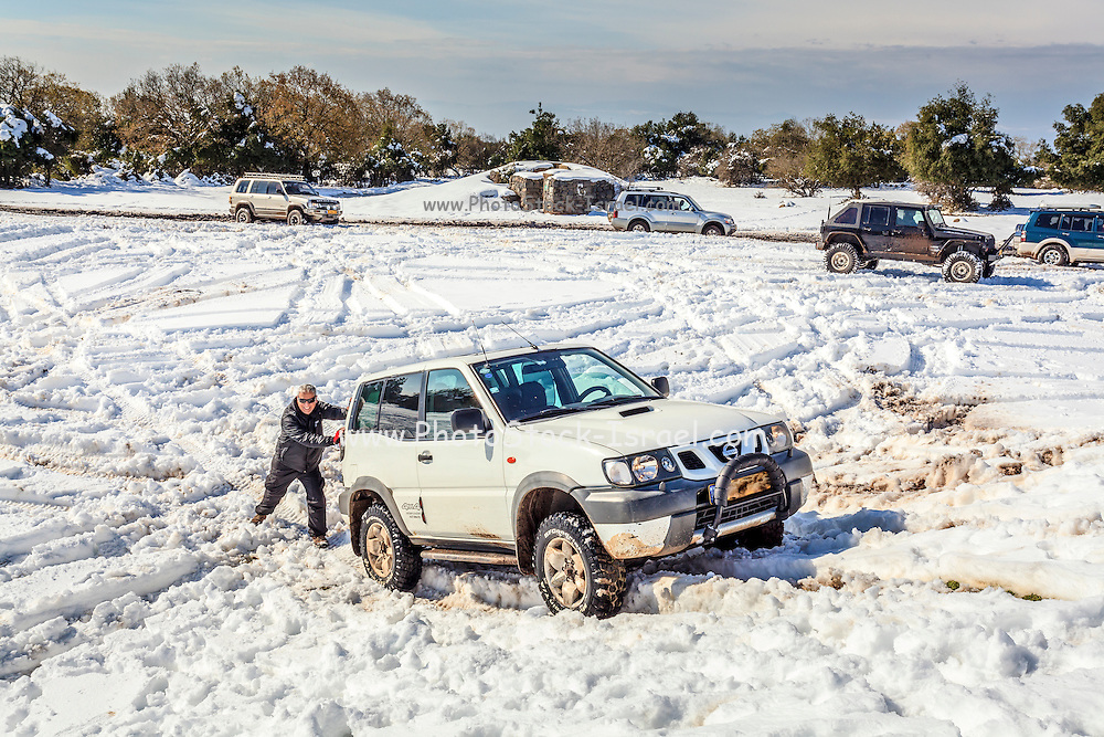 Man pushes a four wheel drive that had stuck in the snow