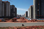 "A view of densely built residential apartment developments near the Kangbashi New District of Ordos City, Inner Mongolia, China on 16 August, 2011. With an investment of over 161billion USD from the local government and revenue from the region's rich coal deposits, enough buildings have risen on the site of an old desert village to hold at least 300,000 residents, complete with ultra modern facilities and grand plazas. The district however is less than 10% occupied, dubbed the ""ghost city"", Kangbashi epitomizes China's real estate bubble and dangers in mindless investment fueled economic  growth. In 2011, the real estate price of Ordos city has dropped over 70%."