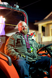 29 January 2016. New Orleans, Louisiana.<br /> A tractor driver waits for the The Krewe of Cleopatra to kick off the main parading season of Mardi Gras in New Orleans with floats filled with riders dispensing beads and throws, marching bands and dance troupes. Families line the streets Uptown to cheer on Cleopatra - 'Throw me something Mister!'<br /> Photo©; Charlie Varley/varleypix.com