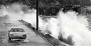 A motorist drives down Beach Drive S.W. near Alki Point as heavy winds and high tide create a pounding surf. (Craig Fujii / The Seattle Times, 1984)