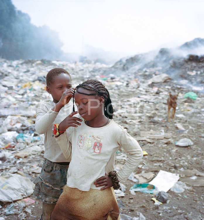 """Alice ( 7)  has her hair  braided by a friend on the dump in a quiet moment between trucks arriving . Alice works every day at the dump with her brother Alan sorting through rubbish for recycling. Florence Her mother lives just 50 metres from the """"California"""" dumpsite in a one-bedroom hut with her five children. None of the children go to school – she feels that it's better that they stay home and help their family to earn a living. They've never had any formal education and neither can read or write. Florence does want her children to improve their situation, but so that they can look after her. The family manages to earn just over a dollar a day from sorting rubbish at the dumpsite but that is not enough to buy food for the family."""