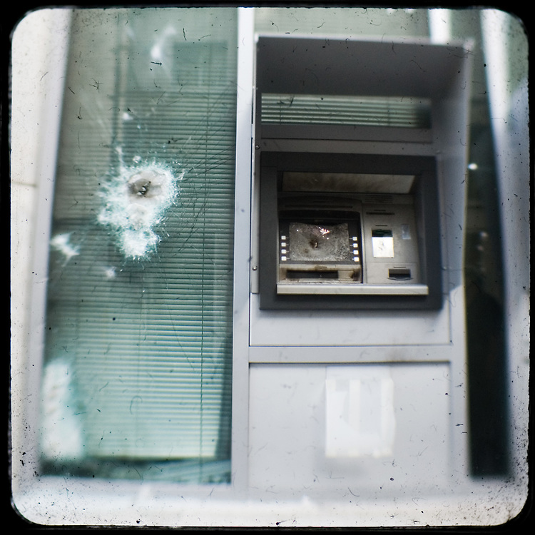 A destroyed ATM in Alexandras avenue, Athens<br /> <br /> Following the murder of a 15 year old boy, Alexandros Grigoropoulos, by a policeman on 6 December 2008 widespread riots, protests and unrest followed lasting for several weeks and spreading beyond the capital and even overseas<br /> <br /> When I walked in the streets of my town the day after the riots I instantly forgot the image I had about Athens, that of a bustling, peaceful, energetic metropolis and in my mind came the old photographs from WWII, the civil war and the students uprising against the dictatorship. <br /> <br /> Thus I decided not to turn my digital camera straight to the destroyed buildings but to photograph through an old camera that worked as a filter, a barrier between me and the city.