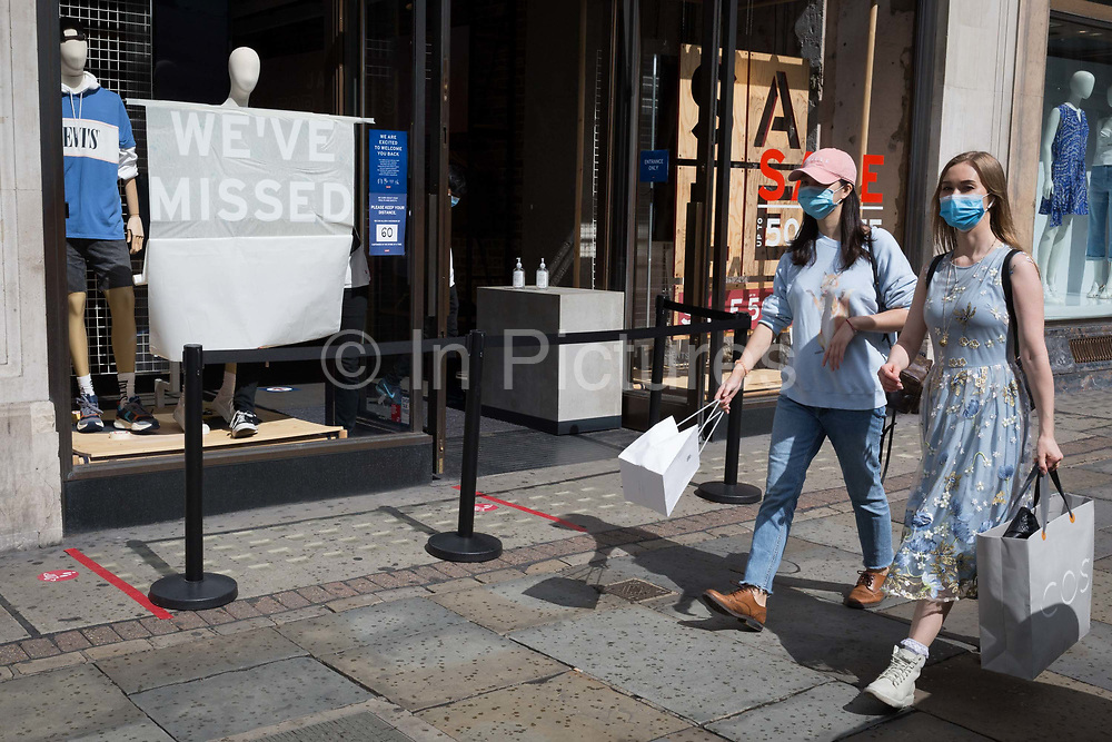 As the UKs Coronavirus lockdown continues to ease, retailers re-open their doors to shoppers, two young women wearing face coverings walk past an employee of a Levis shop on Regent Street who is unpeeling the sticky stencil lettering telling customers that their business has been missed, on 18th June 2020, in London, England.