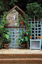 Mirrored woven willow archway with wiggly trellis. Standard bay tree in container.