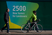 A south London cyclist walks past a regeneration project hoarding at Elephant Park, Elephant & Castle, on 11th October 2016, in London, England. Southwark Council's development partner, Lendlease is regenerating over 28 acres across three sites at the heart of Elephant & Castle, in what is the latest major regeneration opportunity in zone 1 London. The vision for the £1.5 billion regeneration is to build on the area's strengths and vibrant character in order to re-establish Elephant & Castle as one of London's most flourishing urban quarters. The Elephant & Castle regeneration is of a scale rarely seen in central London and includes almost 3,000 new homes, plus office, retail, community, leisure and restaurant space.