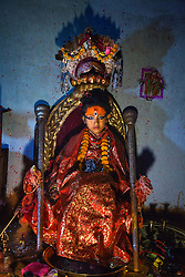 Unika Vajracharya, 6, takes to her throne on her first day as the Kumari of Patan, her feet resting on an offering tray and a snake god guarding her head.