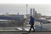 A Kent man walks along West Cliff Promenade that overlooks the Port of Ramsgate, a closed but once busy ferry terminal, on 8th January 2019, in Ramsgate, Kent, England. The Port of Ramsgate has been identified as a 'Brexit Port' by the government of Prime Minister Theresa May, currently negotiating the UK's exit from the EU. Britain's Department of Transport has awarded to an unproven shipping company, Seaborne Freight, to provide run roll-on roll-off ferry services to the road haulage industry between Ostend and the Kent port - in the event of more likely No Deal Brexit. In the EU referendum of 2016, people in Kent voted strongly in favour of leaving the European Union with 59% voting to leave and 41% to remain.