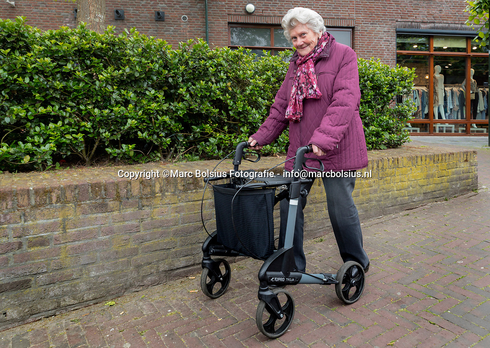 Nederland,  Schijndel, de moeder van Fred,Frank en Rene bezig aan haar dagelijkse wandeling van de Hoofdstraat naar huis aan de Harry Bolsiuslaan.