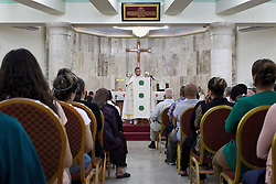 © Licensed to London News Pictures. 27/07/2014. Hamdaniyah, Iraq. An Iraqi Christian priest delivers mass to Iraqi Christians, many of them recent refugees from Mosul, at a church in Hamdaniyah, Iraq.<br /> <br /> Having taken over Mosul Iraq's second largest city in June 2014, fighter of the Islamic State (formerly known as ISIS) have systematically expelled the cities Christian population. Despite having been present in the city for more than 1600 years, Christians in the city were given just days to either convert to Islam, pay a tax for being Christian or leave; many of those that left were also robbed at gunpoint as they passed through ISIS checkpoints. Photo credit: Matt Cetti-Roberts/LNP